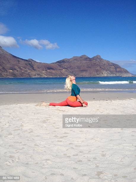 A woman on a beach in one legged pigeon pose