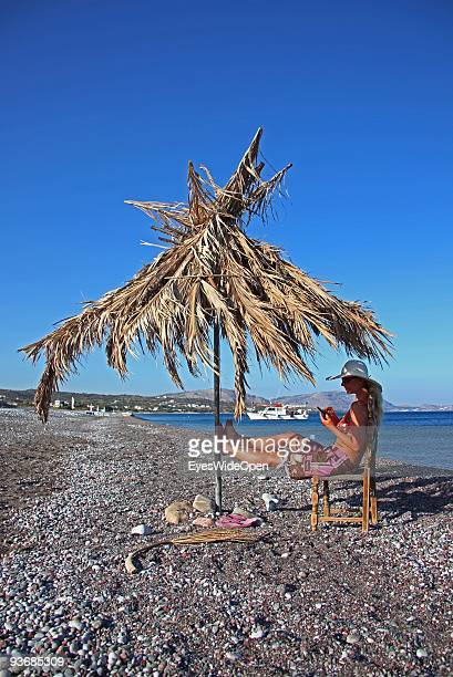 A woman on a beach working with a mobile phone near Lindos on July 16 2009 in Rhodes Greece Rhodes is the largest of the Greek Dodecanes Islands