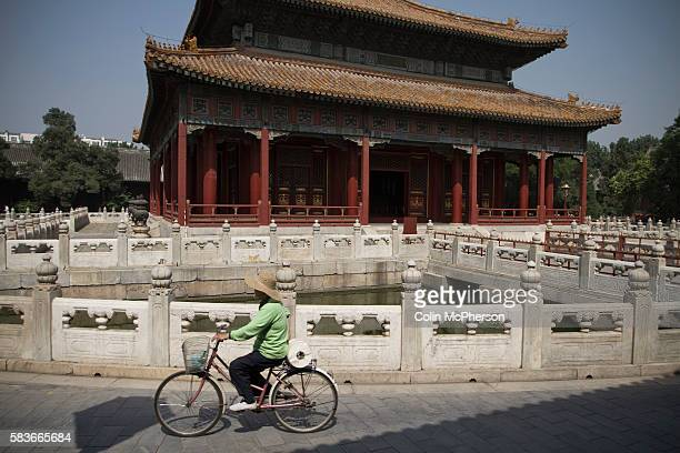 A woman on a bicycle cycling past one of the temples at the Confucius Temple and Guozijian in Beijing China The complex was first built during the...