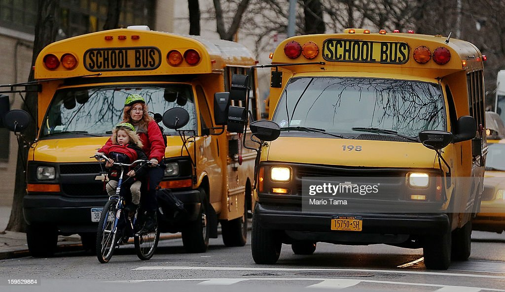 A woman on a bike with a child rides past school buses idling in front of a school in Manhattan's East Village on January 15, 2013 in New York City. Drivers of the city's school buses are set to go on strike tomorrow after negotiations with Mayor Michael Bloomberg failed to reach an agreement; over 150,000 children will need to find an alternate method of transportation to school.