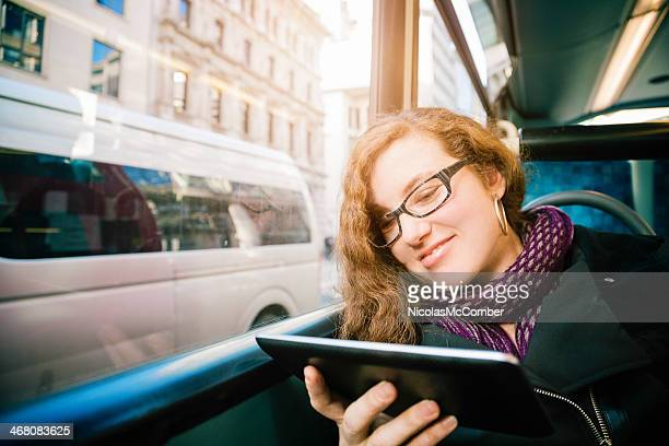 Woman on a bus entertained by digital tablet