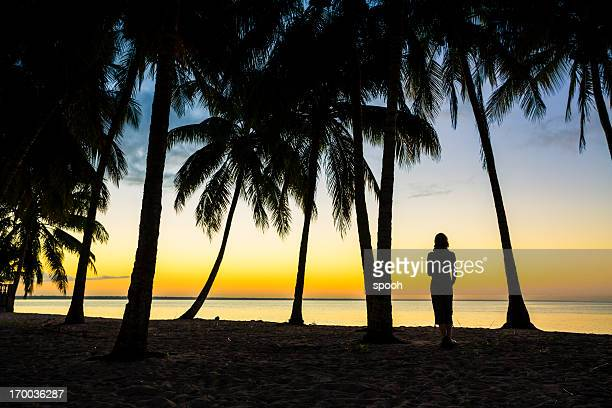 Woman on a carribean beach watching sunrise