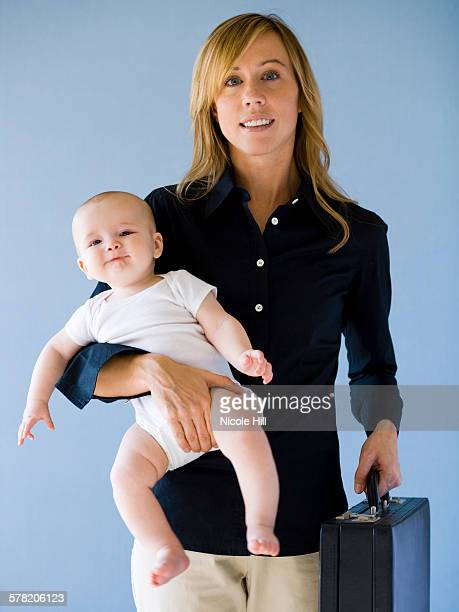 Woman on a cell phone holding a baby.