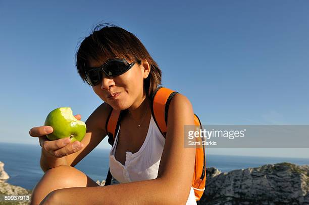Woman on a hike eating an apple