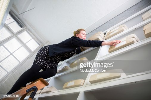 Woman on a ladder reaching for a box out of reach