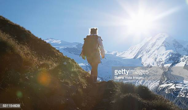 Woman on a mountain trail watching a glacier