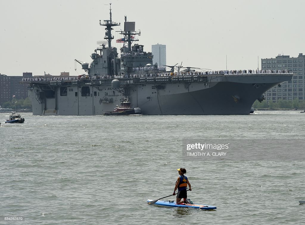 A woman on a paddle boat looks on as sailors and marines stand on the deck of the USS Bataan (LHD 5) as it arrives into Pier 88 during the 'Parade of Ships' ceremony to kick off Fleet Week in New York on May 25, 2016. Thousands of sailors, marines and Coast Guardsmen from the US Navy and US Coast Guard as well as from international Navy ships attend the celebrations. / AFP / TIMOTHY