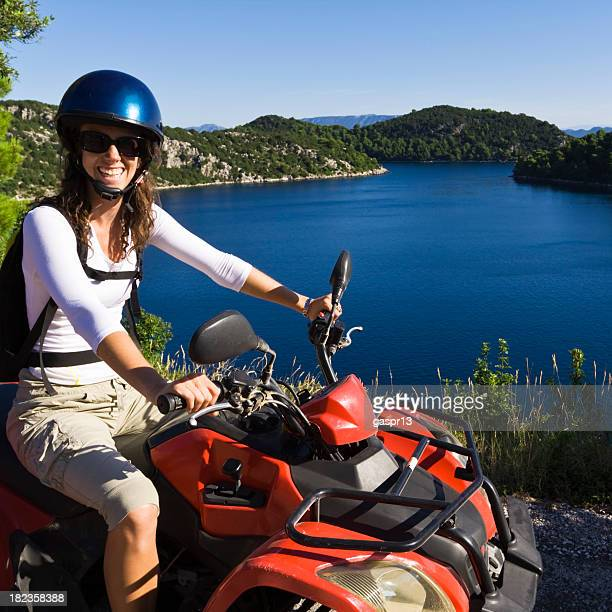 A woman on a red four wheeler sitting in front of blue lake