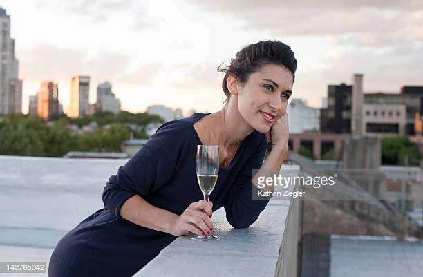 woman on a rooftop, holding glass of champagne