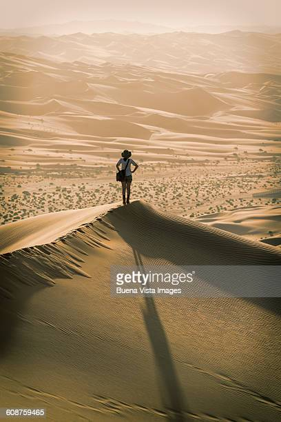 Woman on a sand dune at sunset