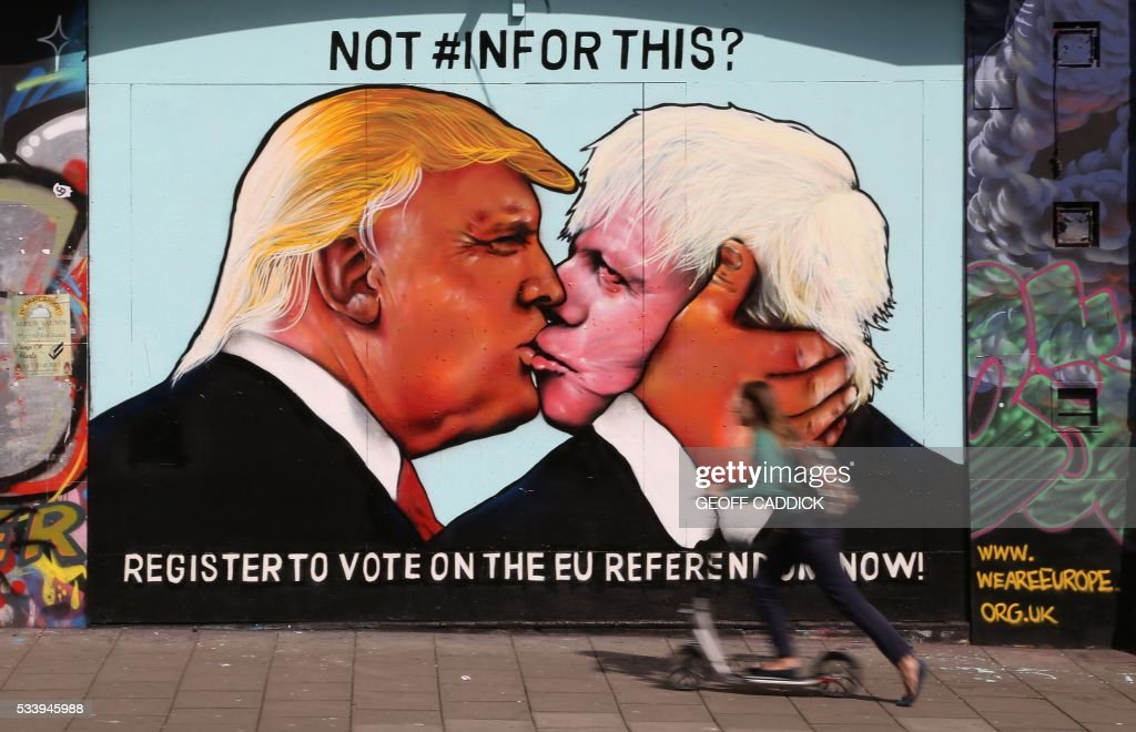 A woman on a scooter passes a mural showing likely US Republican presidential nominee Donald Trump (L) kissing the Former Mayor of London and Conservative MP, Boris Johnson, on the side of a building in Bristol, south west England on May 24, 2016. The mural in Bristol, southwest England, was commissioned by We Are Europe, a campaign group which wants Britain to remain in the European Union at the June 23 vote. / AFP / GEOFF