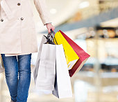 woman with colorful shopping bags walking in modern mall.