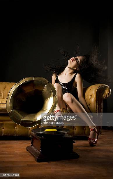 Woman on a sofa swishing her hair in front of a gramophone