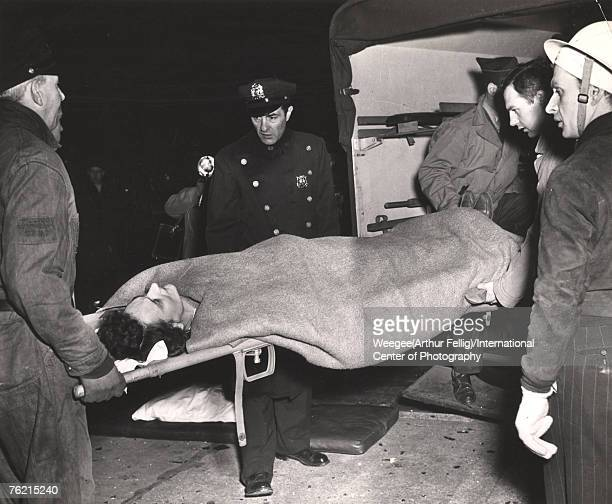 A woman on a strecher is lifted into the back of a vehicle wtched by a police officer a man in a hard had and third man New York New York 1941 Photo...