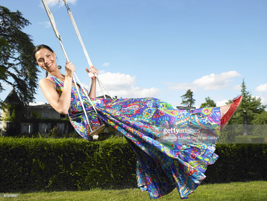 Woman on a swing, blue sky above : Stock Photo