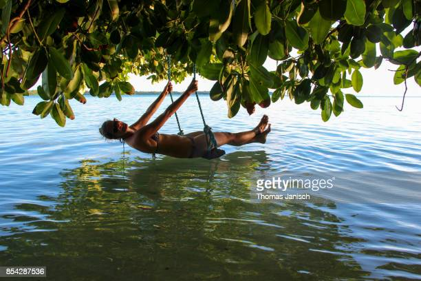 Woman on a swing over the water, Palau