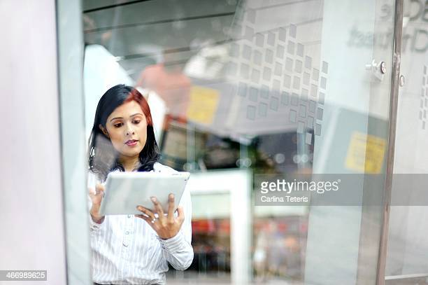 Woman on a tablet behind glass