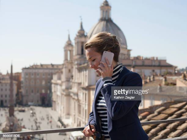Woman on a terrace overlooking Piazza Navona in Rome, talking on mobile phone