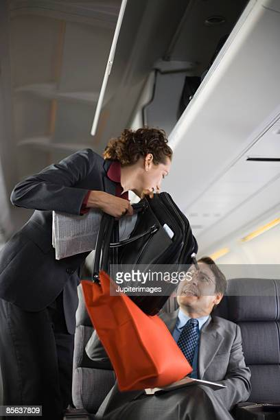 Woman on airplane holding purse and briefcase