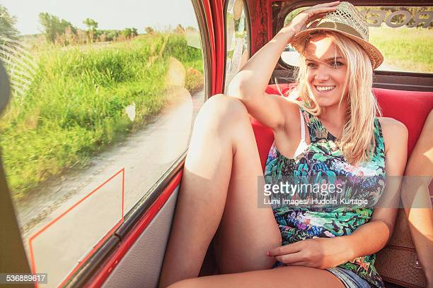 Woman on back seat of vintage car smiling happily