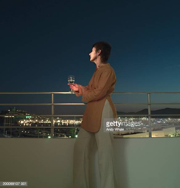 Woman on balcony, holding glass of wine at night