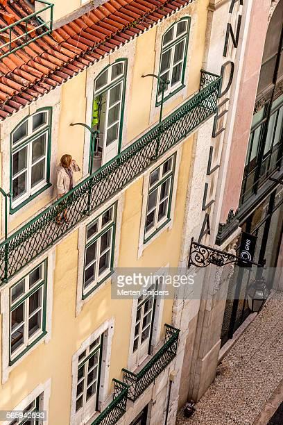 Woman on balcony stalling work