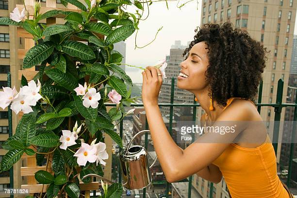 Woman on Balcony Watering Plant