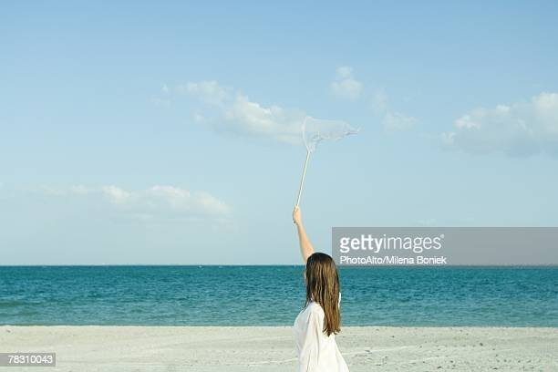 Woman on beach catching clouds with butterfly net, rear view, optical illusion