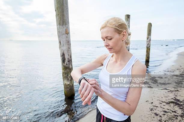 Woman on beach checking running watch