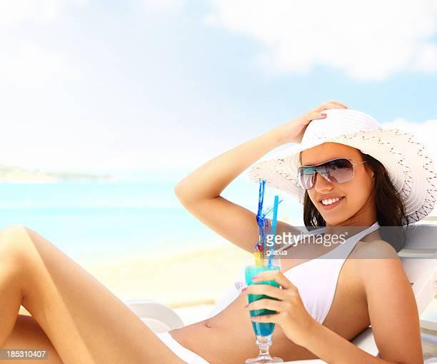 Femme sur la plage après avoir un cocktail.