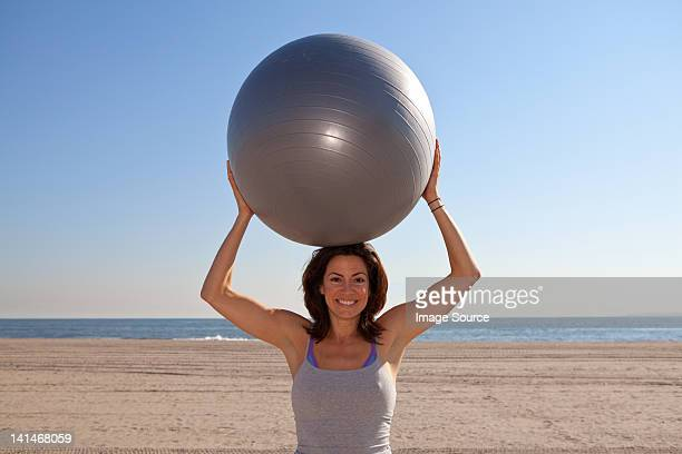 Woman on beach holding exercise ball