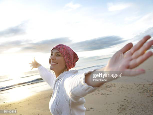 Woman on beach in wither with arms outstretched