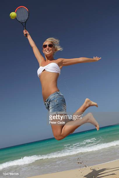 woman on beach jumping to hit tennis ball