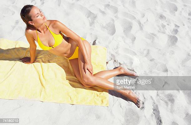 Woman on beach towel sunbathing