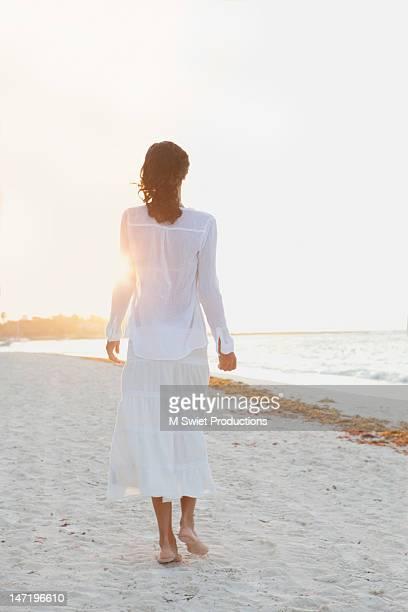 woman on beach  walking at sunrise
