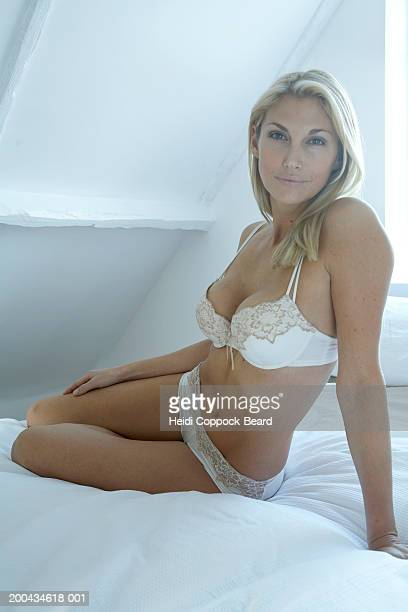 Woman on bed in lingerie smiling, portrait, close-up
