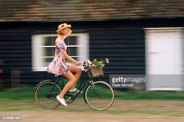 Woman on bicycle with basket of flowers, holding hat on with hand