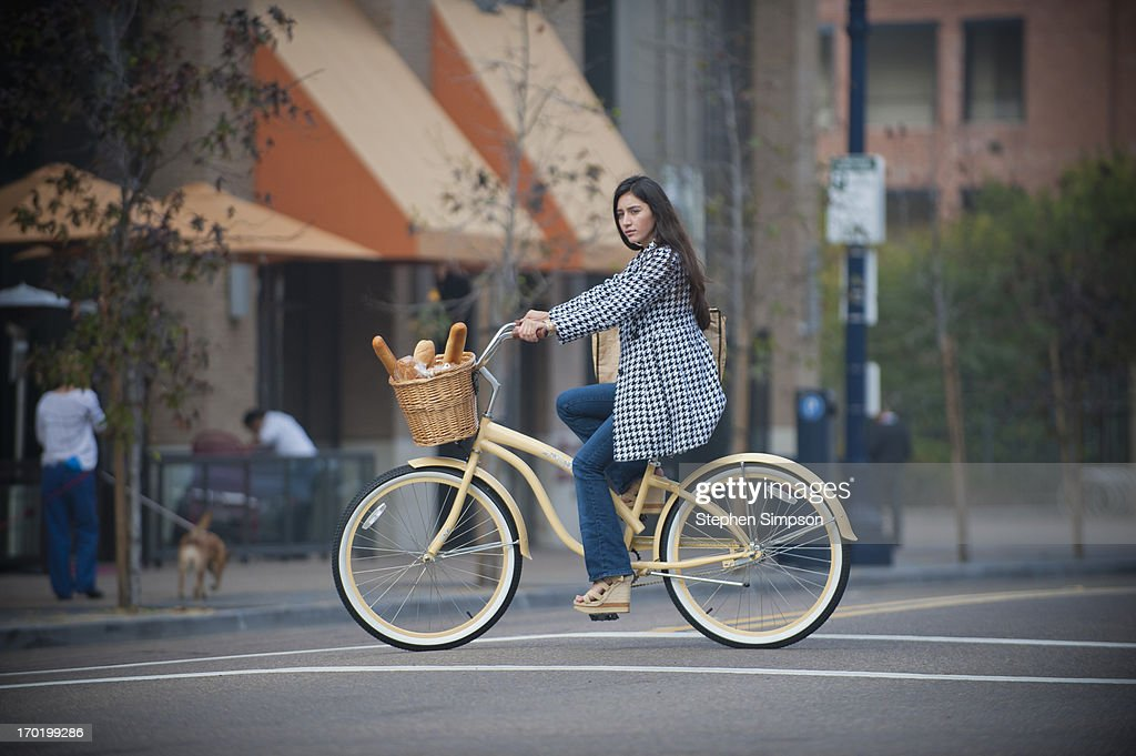 woman on bike with loaves of fresh bread : Stock Photo