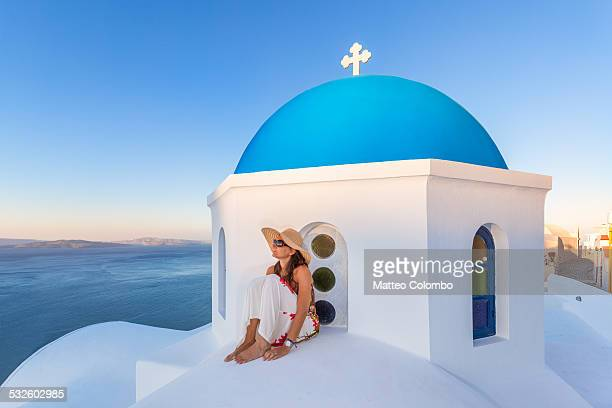 Woman on blue domed church in Santorini, Greece