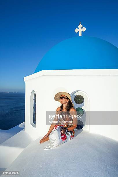 Woman on blue domed church, Oia, Santorini, Greece