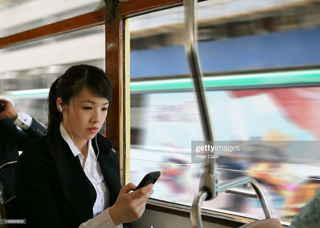 woman on bus looking at phone : Stock Photo