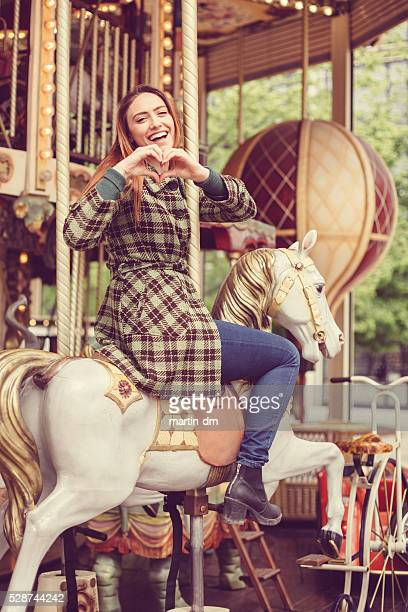 Woman on carousel showing love symbol to his boyfriend