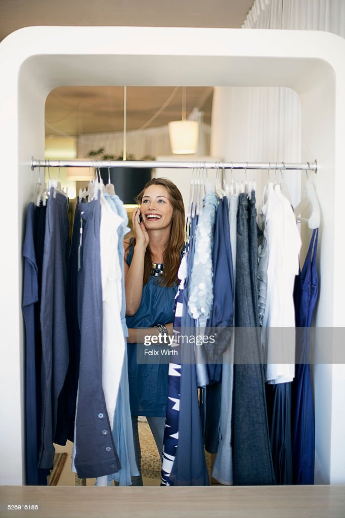 Woman on cell phone at clothing rack : Photo