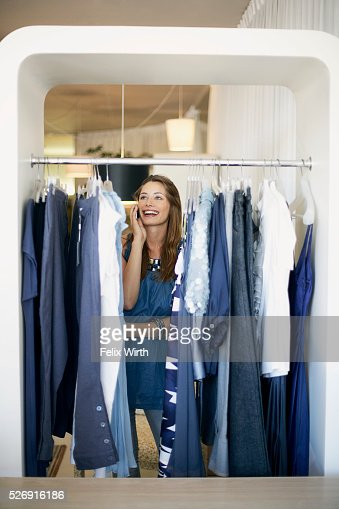 Woman on cell phone at clothing rack : Foto de stock