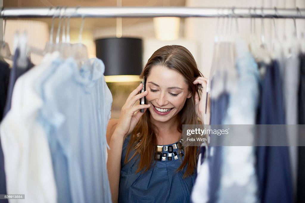 Woman on cell phone in clothing store : Photo