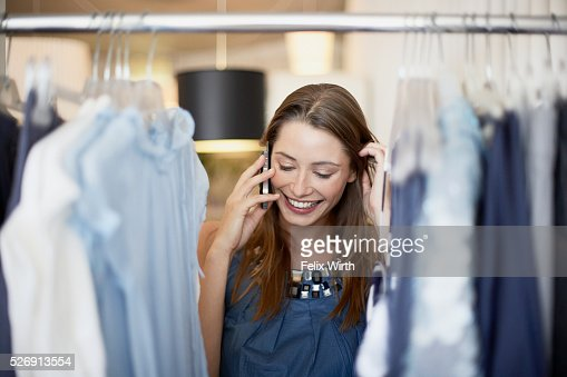 Woman on cell phone in clothing store : Stock Photo