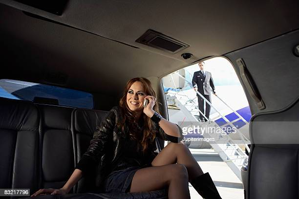 Woman on cell phone in limo at airport