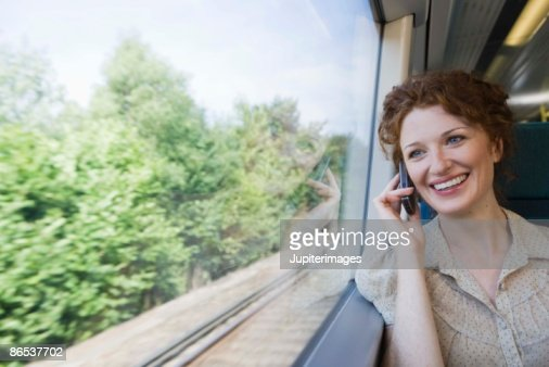 Woman on cell phone in train : Foto stock
