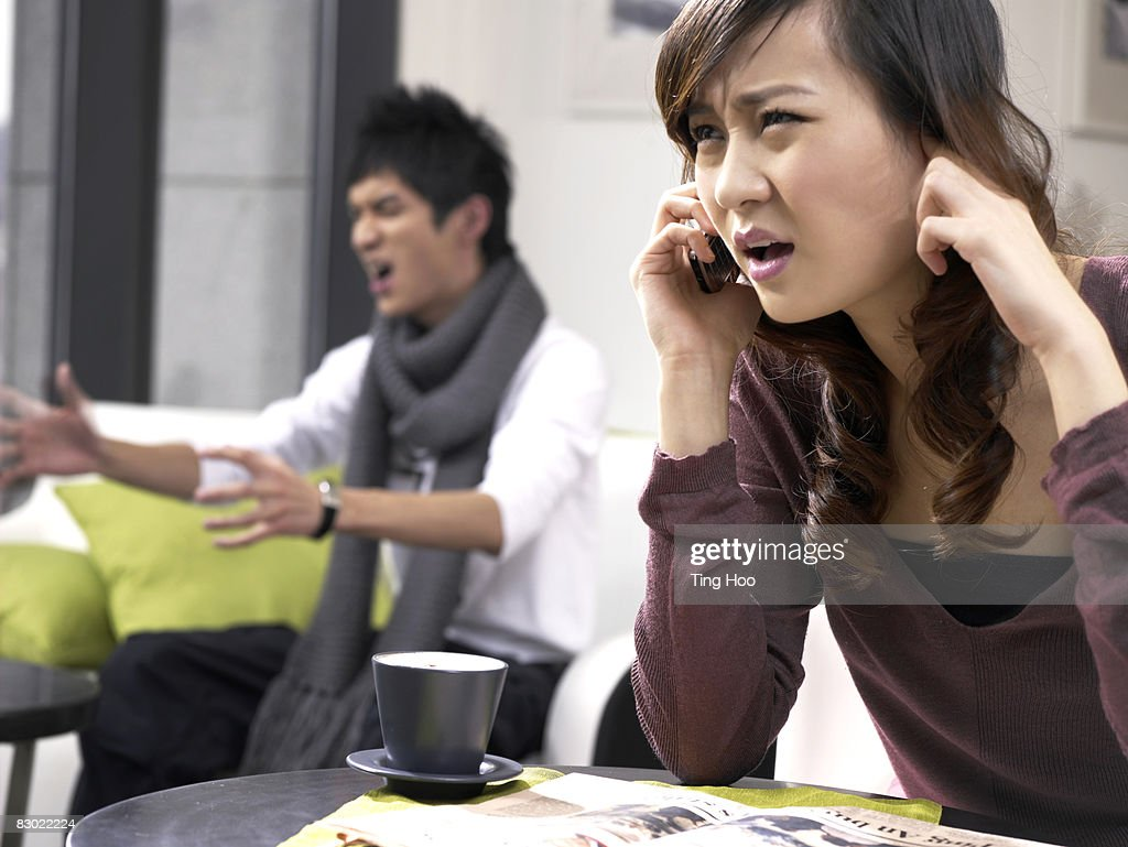 Woman on cell phone, man yelling in background : Stock Photo