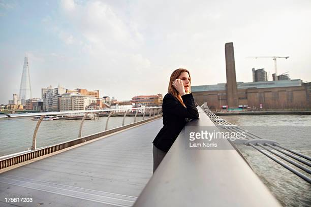 Woman on cell phone on Millennium Bridge, London, England, UK